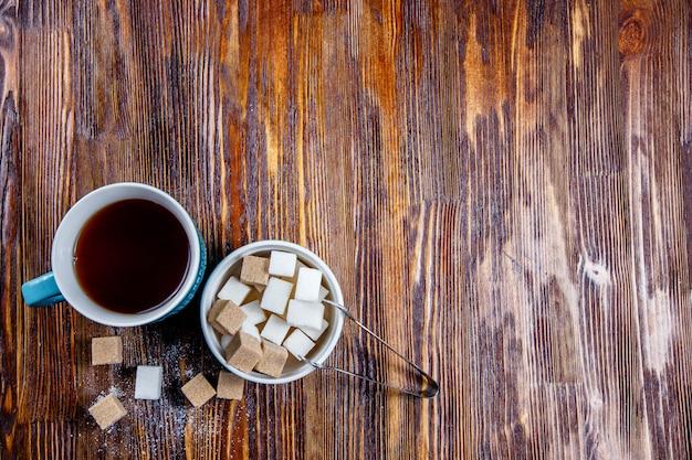 Açúcar marrom e branco no prato ou prato e chá em um copo
