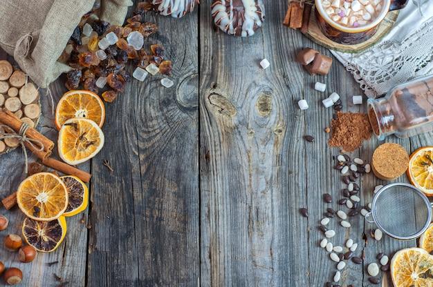 Açúcar mascavo, doces e um copo com uma bebida em uma superfície de madeira velha