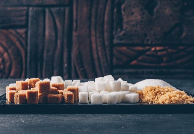 Açúcar mascavo e branco em uma placa de corte. vista lateral.