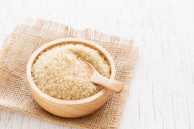 Açúcar mascavo e colher de madeira em tigela marrom na mesa de madeira branca