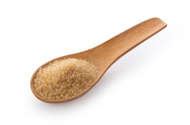 Açúcar mascavo em colher de pau na parede branca