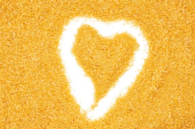 Açúcar mascavo, em forma de coração, close-up, macro, vista de cima.