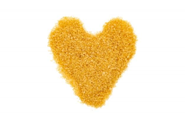 Açúcar mascavo, em forma de coração, isolado, close-up, macro, vista superior.