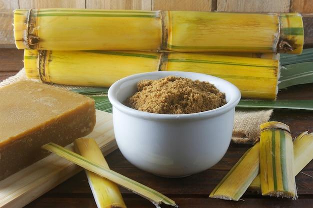 Açúcar mascavo orgânico artesanal granulado de cana-de-açúcar em uma tigela na mesa de madeira da refinaria rústica. vista frontal