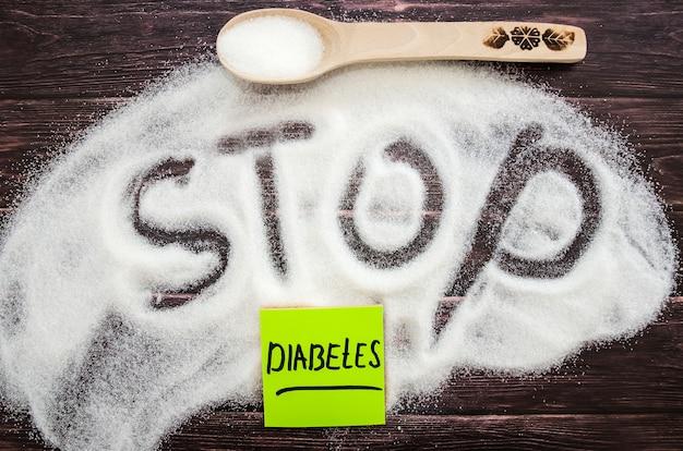 Açúcar na areia com uma colher de pau e a palavra parar no açúcar. o conceito de diabetes e os malefícios do açúcar