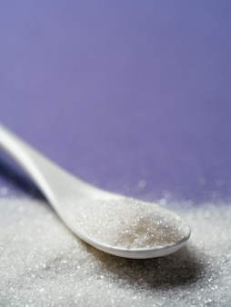 Açúcar na colher branca na violeta, copie o espaço