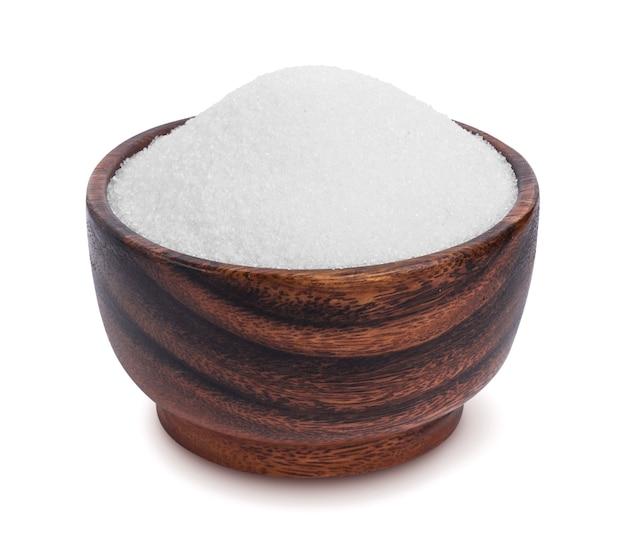 Açúcar na tigela de madeira isolada no fundo branco
