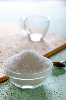 Açúcar na tigela de vidro com fundo de madeira
