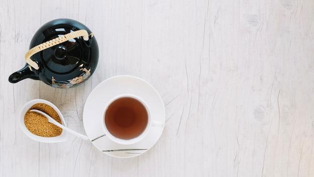 Açúcar perto de um copo de chá e bule