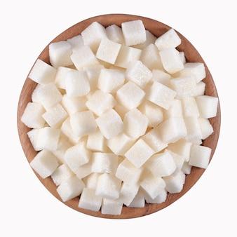 Açúcar refinado em uma tigela de madeira em um fundo branco