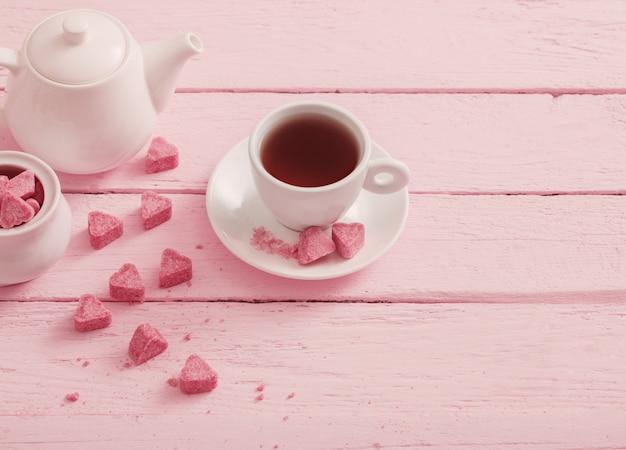 Açúcar rosa granulado em forma de coração e xícara de chá em um fundo de madeira