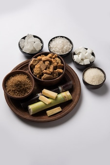 Açúcar, variedade de açúcar e cana-de-açúcar - subprodutos da cana-de-açúcar ou ganna colocados sobre fundo temperamental. foco seletivo