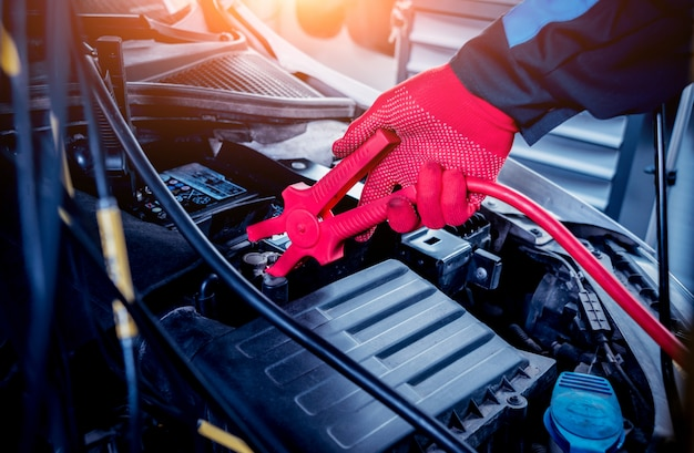 Acumulador de carregamento. mãos e terminais. reparo do carro.