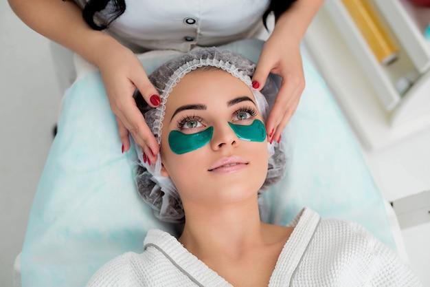 Acupressão, massagem nas têmporas, flocos verdes de colágeno. procedimento cosmético, o rosto da mulher com flocos verdes sob os olhos.
