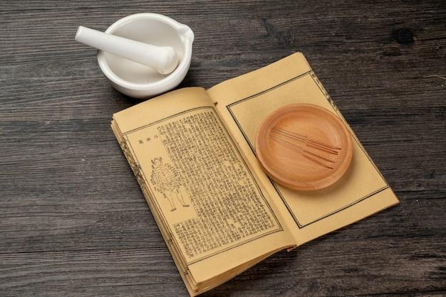 Acupuntura, moxabustão e livros médicos da medicina tradicional chinesa Foto Premium