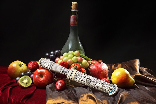 Adaga velha na bainha, natureza morta holandesa clássica com garrafa de vinho empoeirada e frutas em um azul escuro, horizontal