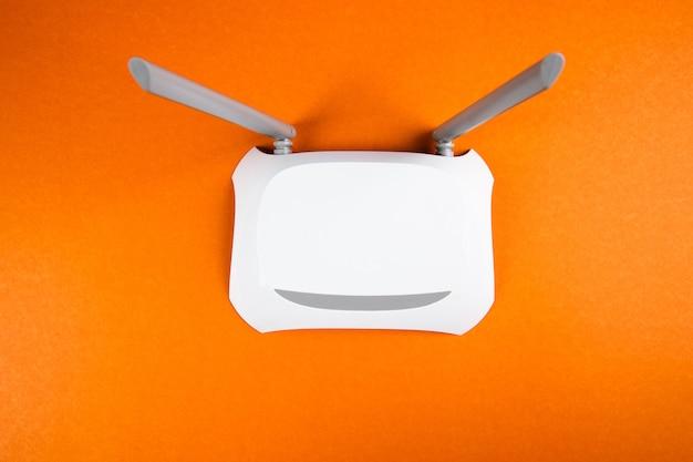 Adaptador wi-fi branco em uma superfície laranja