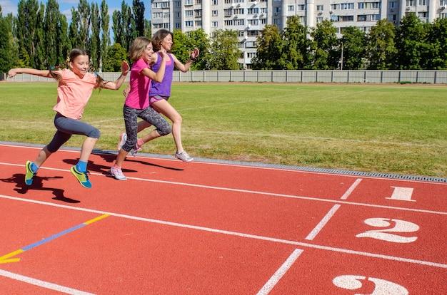 Adequação da família, mãe e filhos correndo na pista do estádio, exercício com crianças e conceito de estilo de vida saudável do esporte