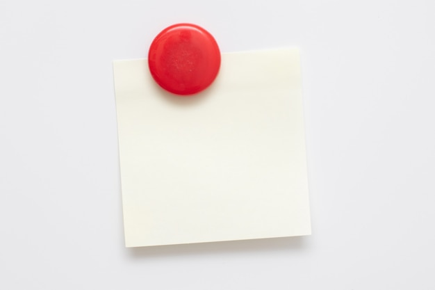 Adesivo amarelo anexado ímã vermelho na geladeira branca.