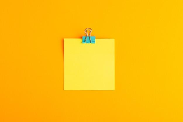 Adesivo amarelo de vista superior vazio na superfície laranja