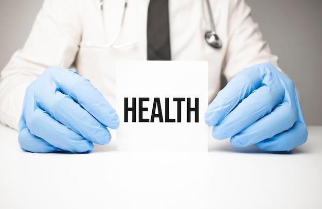 Adesivo branco com o texto saúde nas mãos do médico com um estetoscópio Foto Premium