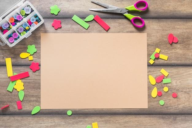 Adesivo colorido com forma diferente perto do papel marrom na mesa de madeira