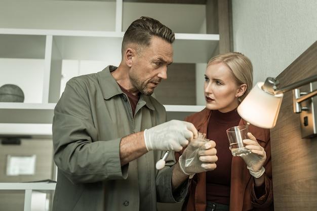 Adesivo com impressões digitais. casal atraente de investigadores discutindo impressões digitais de um copo d'água guardando-o na bolsa