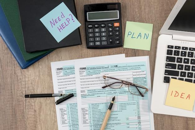 Adesivo com texto precisa de ajuda, calculadora e formulário de imposto de 1040 ondesk no escritório. conceito de imposto