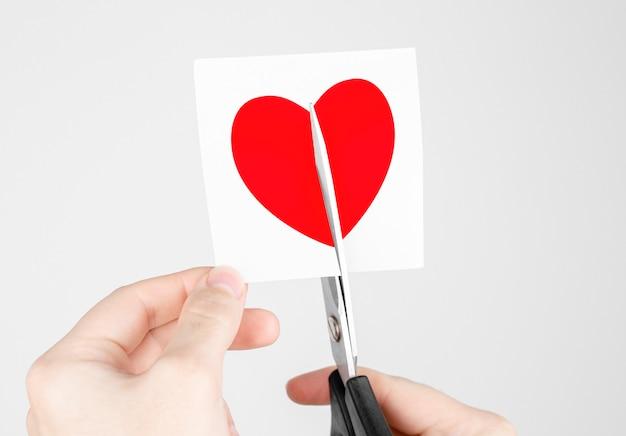 Adesivo de homem cortando tesoura com coração vermelho