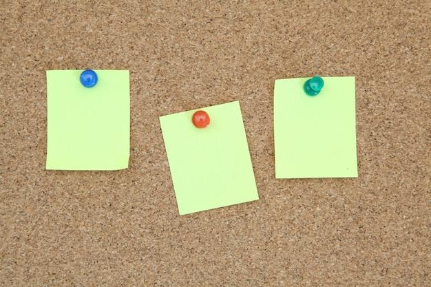 Adesivo de memorando três amarelo na placa de aviso de cortiça
