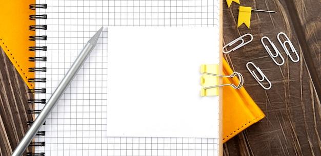 Adesivo no caderno com lápis sobre fundo de madeira