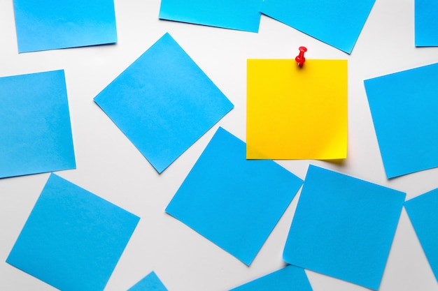 Adesivo pegajoso amarelo em branco sobre um fundo branco para lembrar informações, anexado com um clipe de papel. há adesivos azuis vazios ao lado dele.