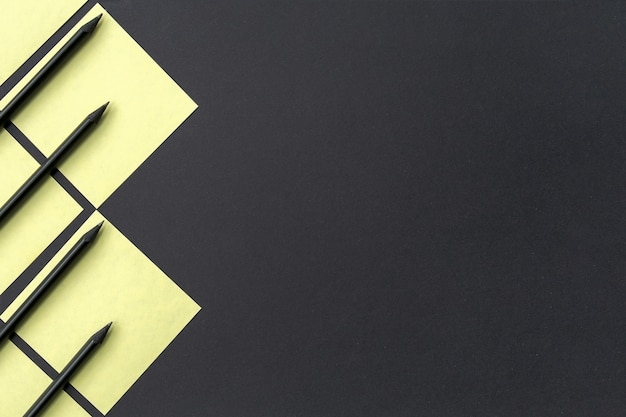 Adesivos amarelos com lápis pretos forrados com um padrão geométrico em preto