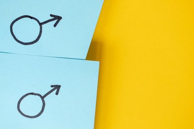 Adesivos azuis com símbolos de gênero de marte acima do fundo amarelo