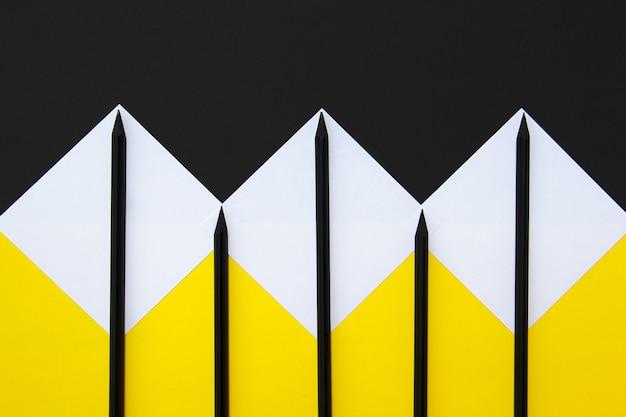 Adesivos brancos com lápis pretos forrados com um padrão geométrico de amarelo e preto