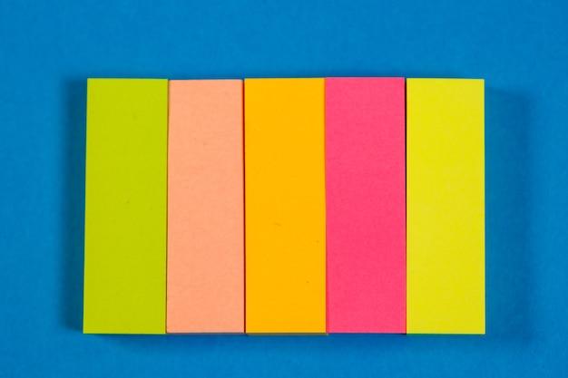 Adesivos coloridos para notas em um fundo colorido