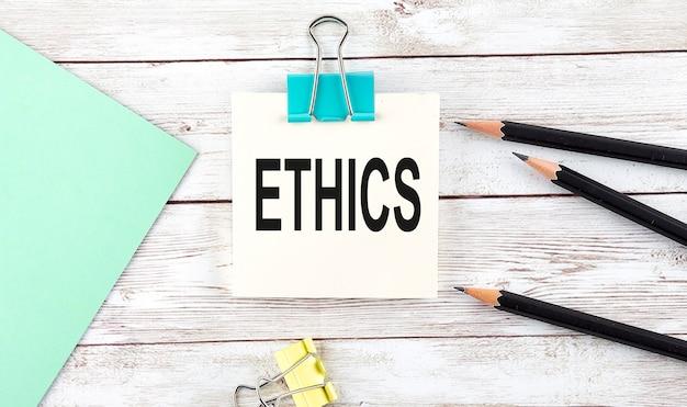 Adesivos com lápis e caderno com texto ética na superfície de madeira