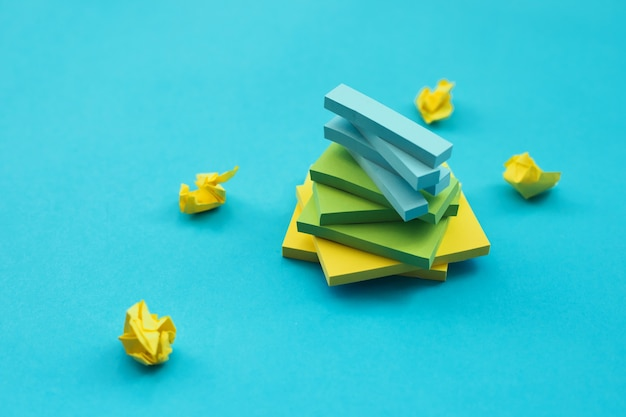 Adesivos de diferentes tamanhos e cores repousam sobre uma parede azul em forma de torre. blocos de notas para notas e lembretes.