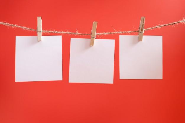 Adesivos de lembrete brancos sobre um fundo vermelho. folhas de papel em branco para desejos e objetivos.