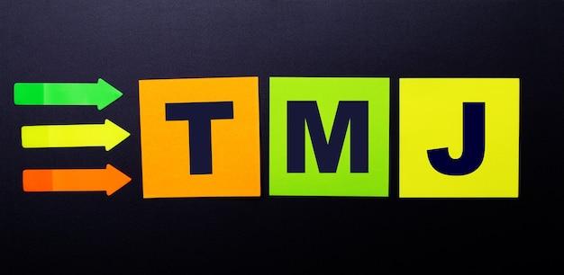 Adesivos de papel colorido brilhante em uma superfície preta com o texto tmj