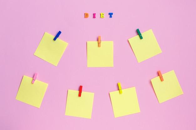 Adesivos de papel colorido no fundo rosa