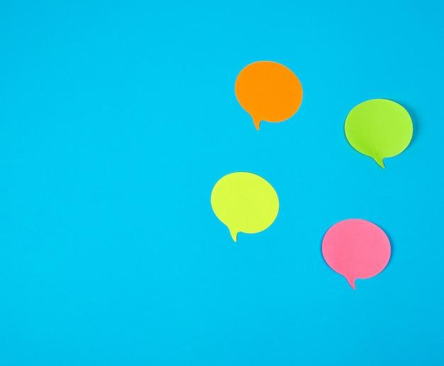 Adesivos de papel de cor sobre um fundo azul, close-up