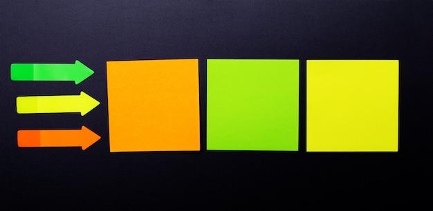 Adesivos de papel transparente sortido multicolorido brilhante em uma parede preta. copiar localização