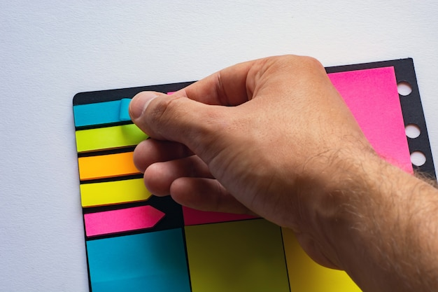 Adesivos multi-coloridas para notas de diferentes tamanhos e formas com um marcador.
