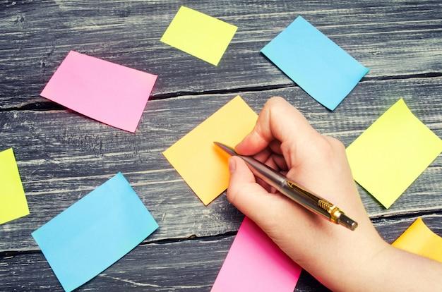 Adesivos pegajosos para notas sobre um fundo preto de madeira. gerenciamento de tempo