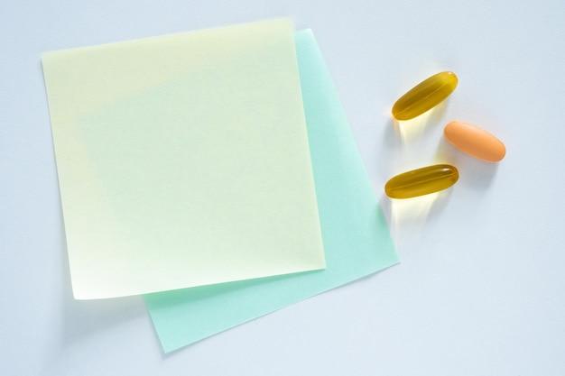 Adesivos vazios para preenchimento de receita de comprimidos e muitas cápsulas na mesa, vista de cima, layout plano