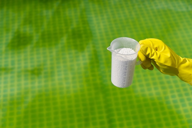 Adição de pó de cloro na piscina para remover algas e desinfetar a água. conceito de cuidados de piscina inflável.