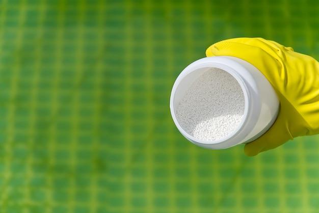 Adição de pó de cloro na piscina para remover as algas e desinfetar a água.