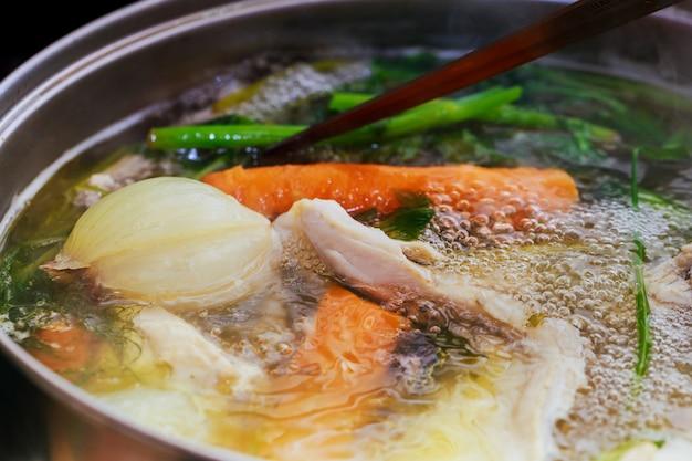 Adicionando asas de frango em uma panela. cozinhar caldo de galinha.