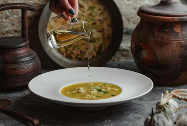 Adicionando azeite à sopa de caldo de galinha.